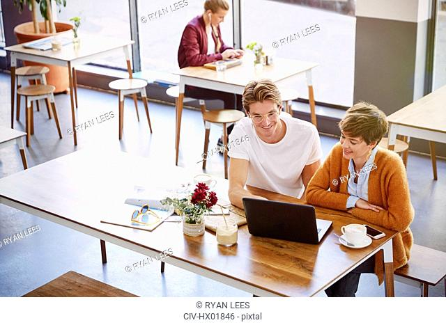 Business people drinking coffee meeting using laptop in cafe