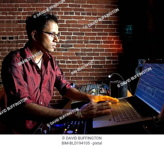 Indian man typing on laptop