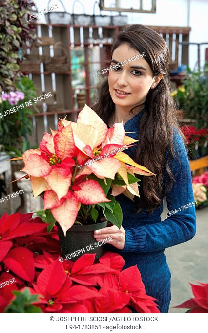 Portrait of a 21 year old brunette woman shoopping in a plant nursery, holding a poinsettia plant