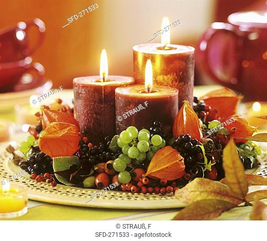 Candles on plate in wreath of physalis and fruit