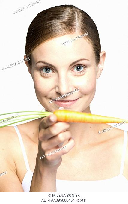 Young woman balancing carrot on hand, portrait