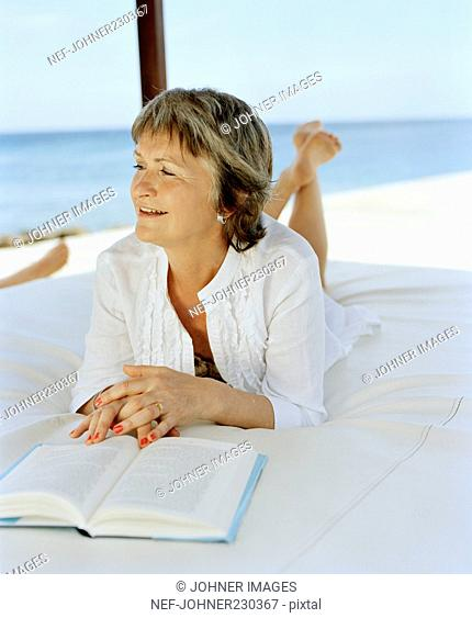Woman lying on a bed and reading