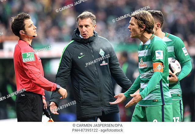 Bremen's captain Clemens Fritz (R) and sports director Frank Baumann talk with referee Lasse Kozlowski (L) during the German Bundesliga soccer match between...