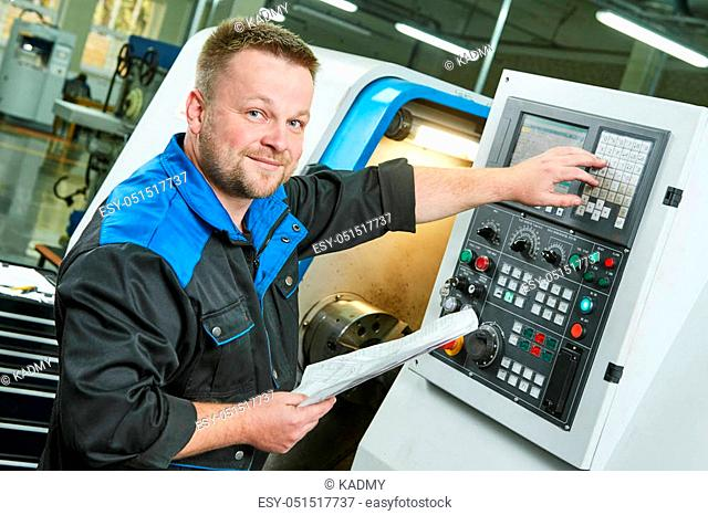 Industrial factory worker or service engineer operating cnc turning lather machine at factory in metal machining industry