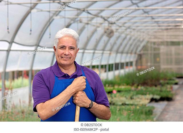 Senior man working in garden centre, portrait