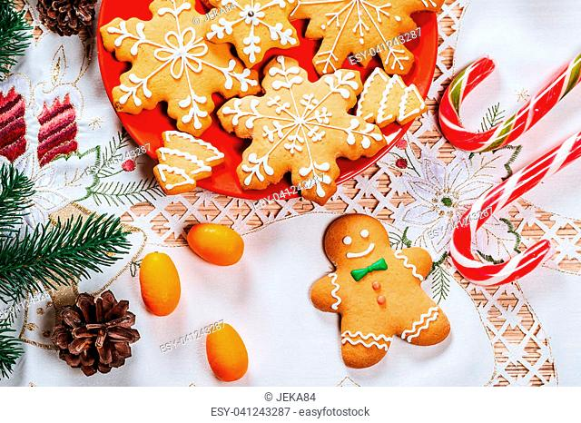 Christmas gingerbread cookies homemade on red plate with branches of Christmas tree and decor on home New Year table. Merry Christmas postcard