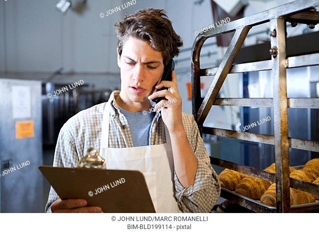 Caucasian baker talking on telephone in bakery
