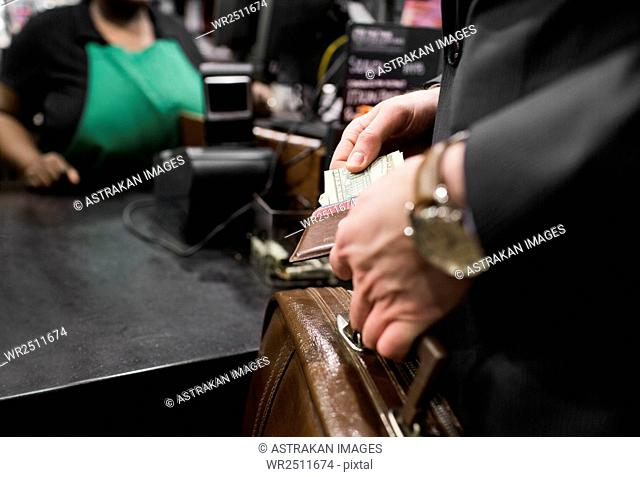 Cropped image of businessman keeping money in wallet at stall