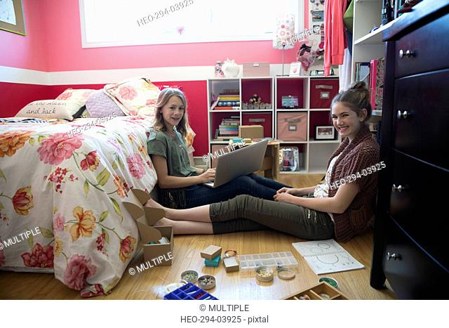 Portrait smiling girls with laptop making jewelry on bedroom floor