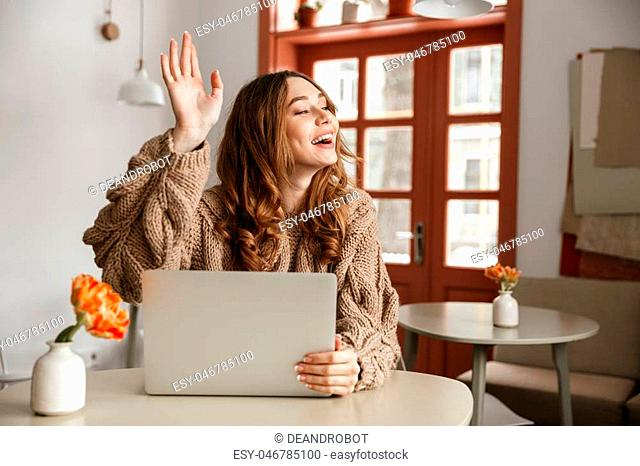 Portrait of a smiling young woman waving her hand while sitting at the table with laptop computer indoors