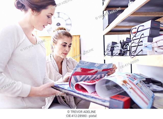 Interior designers browsing fabric swatches in office