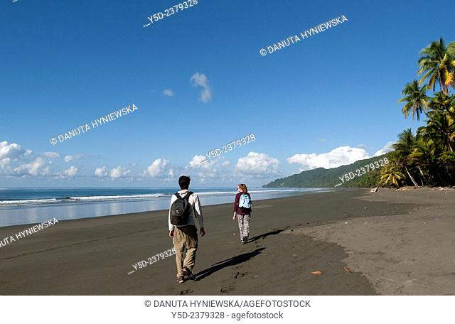 young tourists walking empty beach, wild coast of the Pacific Ocean, Corcovado National Park, Costa Rica,