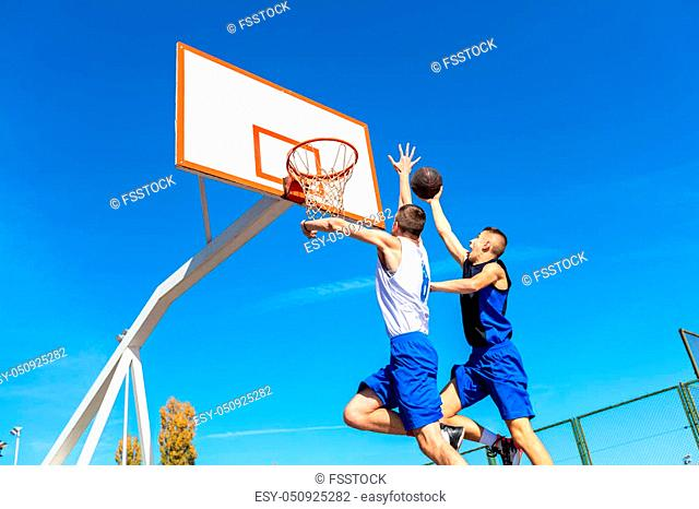 Young Basketball street player making slam dunk