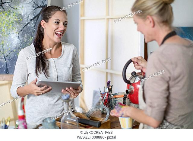 Woman with digital tablet talking with girlfriend