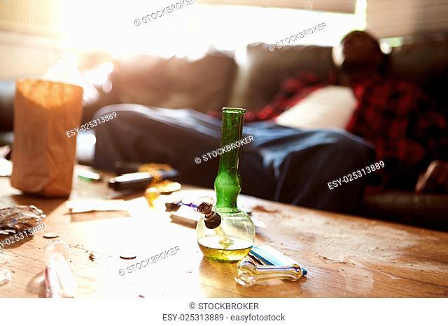 Man Slumped On Sofa With Drug Paraphernalia In Foreground