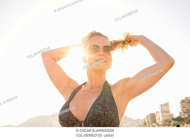 Sunlit portrait of woman tying back hair at beach, Alicante, Spain