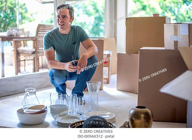 Moving house: man preparing to pack glassware