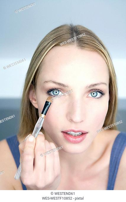 Young woman applying eye shadow, portrait