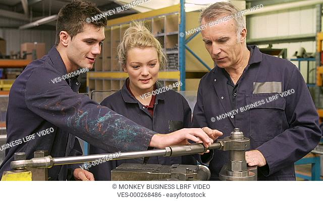 Engineer explaining to male and female apprentices how to operate hydraulic pipe bending machine as they ask questions.Shot on Sony FS700 in PAL format at a...