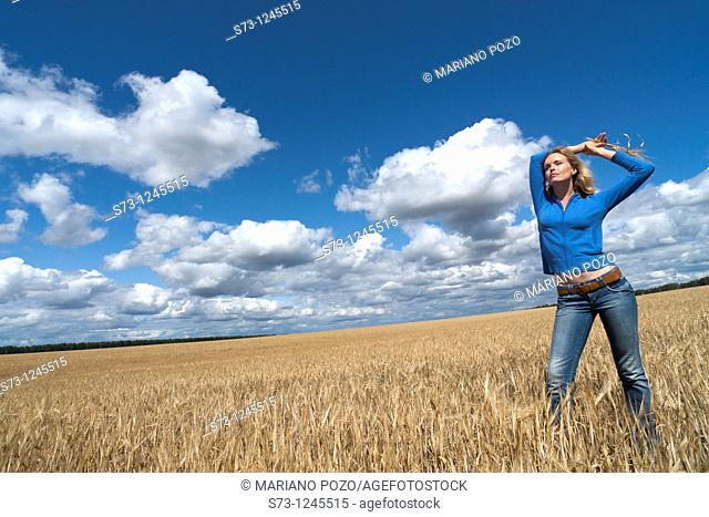 Young woman in a wheat field in a russian village, Kirillovka, Russian Federation