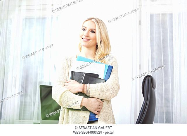 Portrait of smiling blond woman holding documents