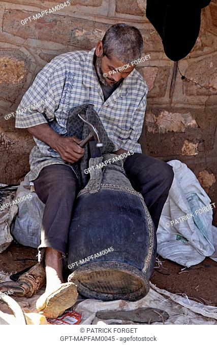 A SHOEMAKER WORKING WITH LEATHER IN THE BAZAAR, BERBER MARKET OF TAHANAOUTE, AL HAOUZ, MOROCCO