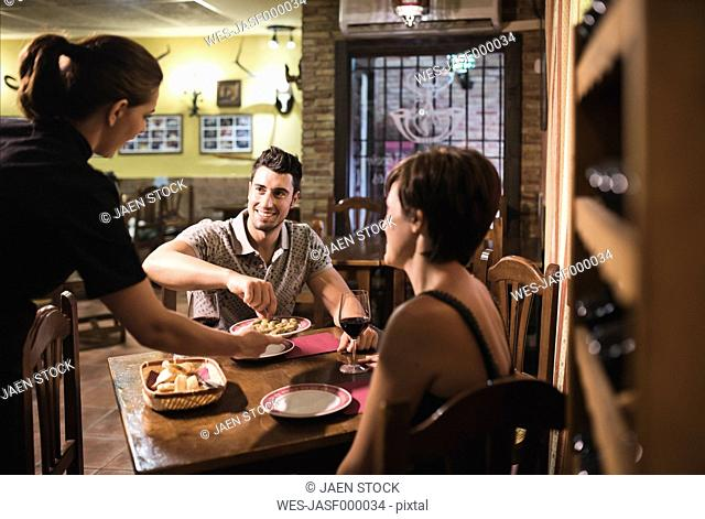 Waitress serving olives to couple in traditional Spanish bar