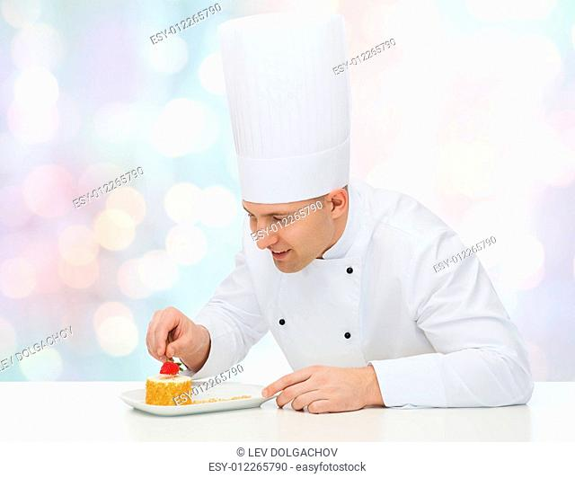 cooking, profession, haute cuisine, food and people concept - happy male chef cook decorating dessert over blue lights background