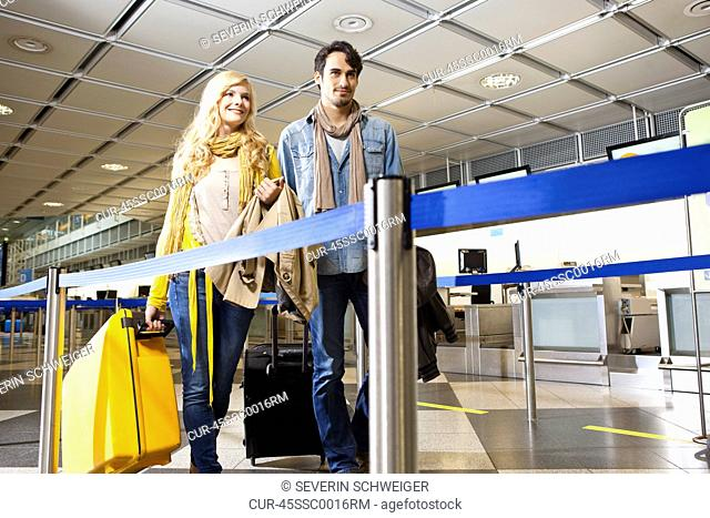 Couple rolling luggage in airport
