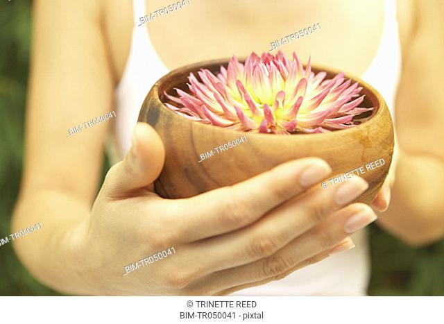 Close up of woman's hands hold bowl with flower in it