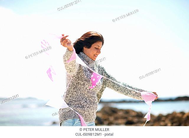 Woman at coast holding bunting