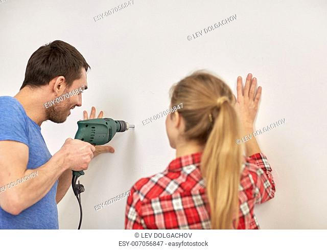 building, repair and people concept - happy couple with electric drill perforating wall at home