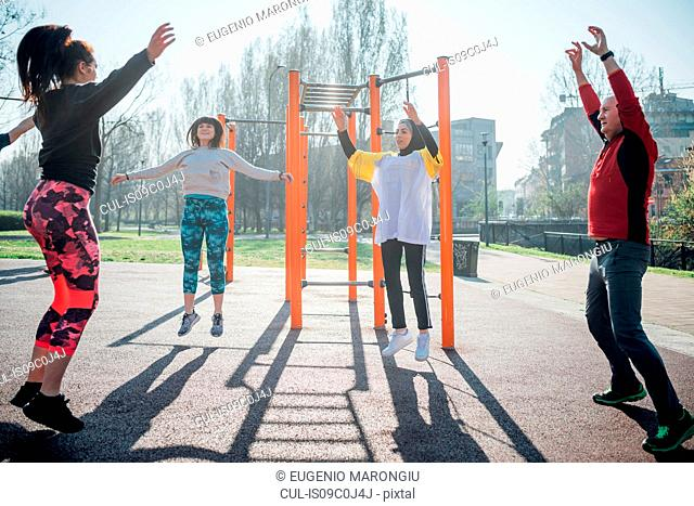 Calisthenics class at outdoor gym, man and women jumping