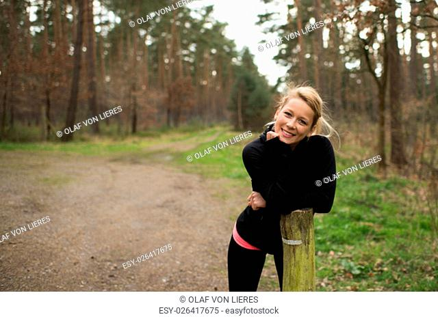 satisfied jogger based in the forest on a wooden pillar