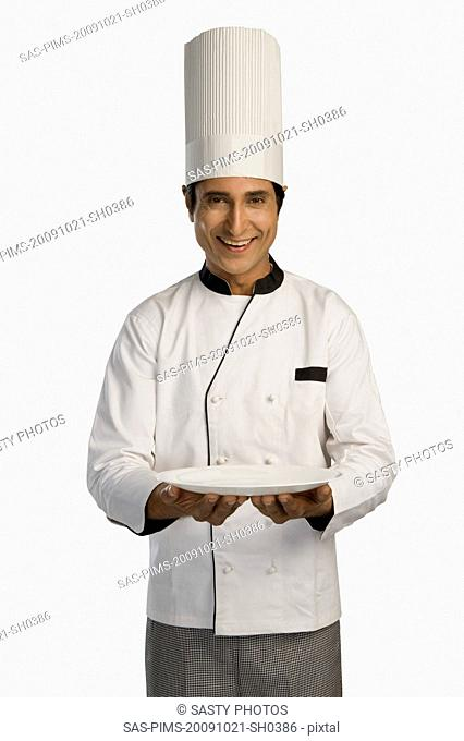 Portrait of a chef holding a plate and smiling