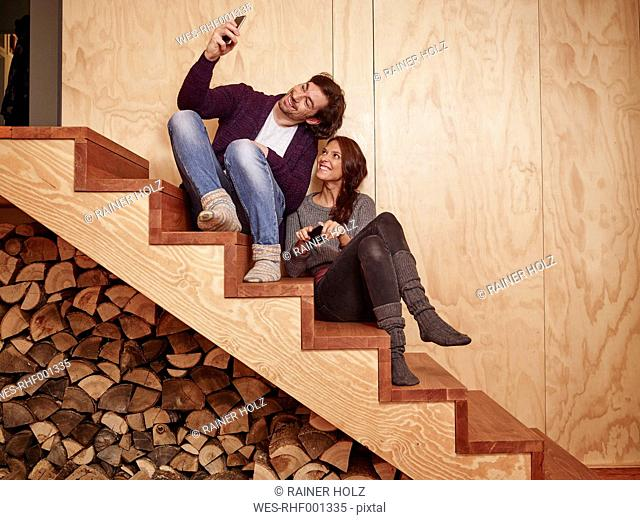 Happy couple sitting on wooden stairs using smart phone