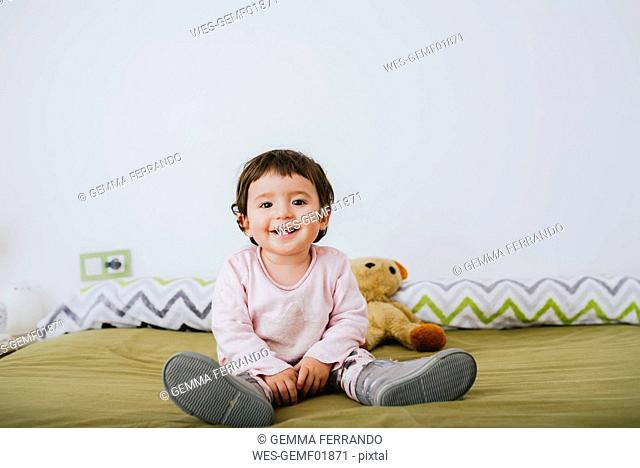 Portrait of happy baby girl sitting on bed