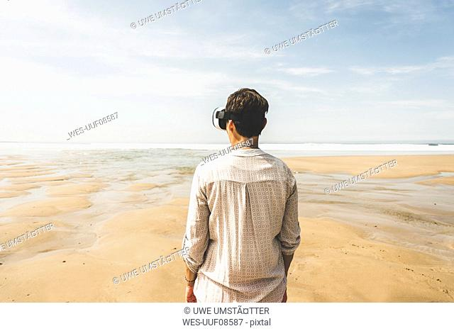 Mature woman standing on the beach wearing VR glasses