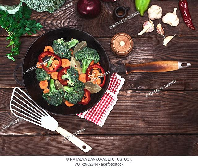 fresh vegetables in a black round frying pan on a brown wooden background, vintage toning, top view