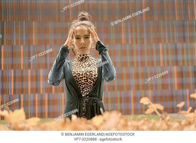 fashionable woman touching head, in front of geometrical pattern, line, in Munich, Germany