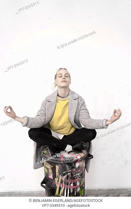 young woman meditating on trash can with creative painting, in Germany