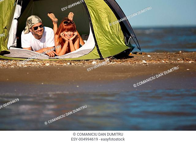 happy young couple sitting in tent seaside