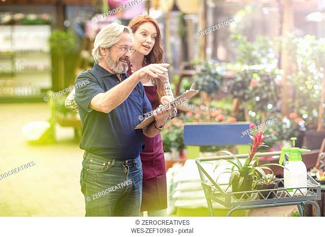 Manger and gardener discussing in garden center