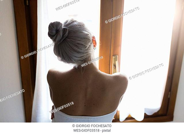 Rear view of young woman with hair bun looking out of window