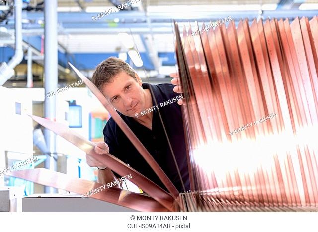 Worker inspecting circuit board base layers in circuit board factory