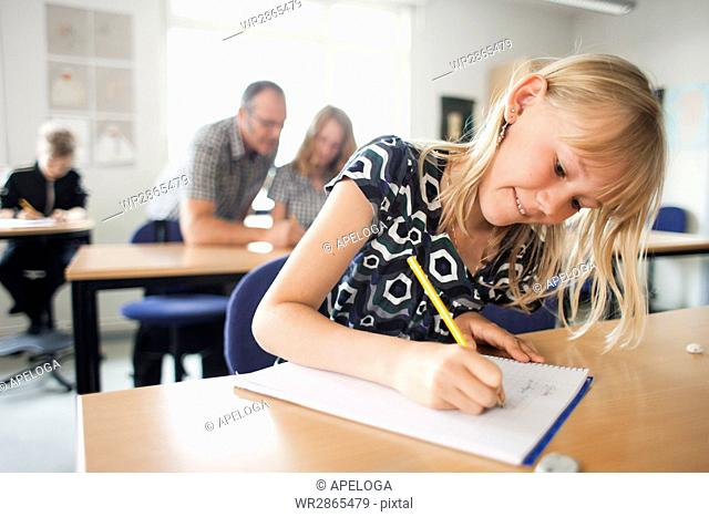 Girl writing on book with professor and students in classroom