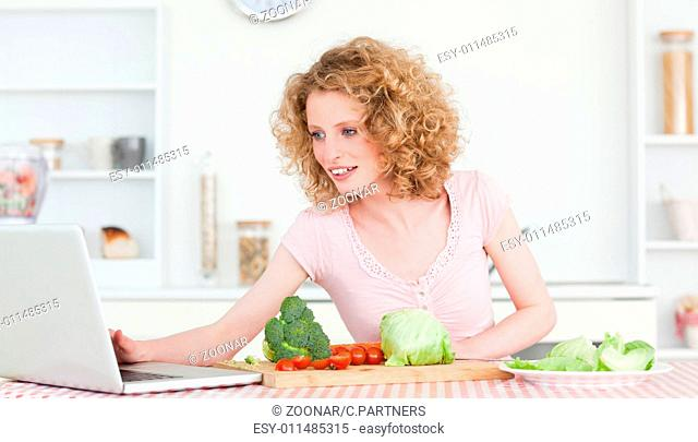 Good looking blonde woman relaxing with her laptop while cooking some vegetables in the kitchen