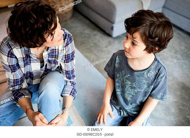Mother and son at home, sitting on floor, talking