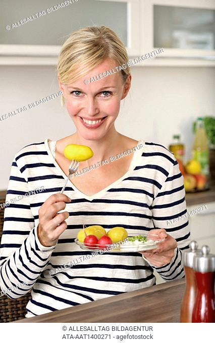 Woman is eating potatoes with cottage cheese