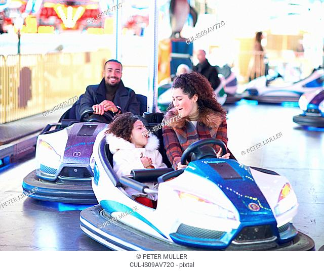 Mother and daughter in bumper car face to face smiling